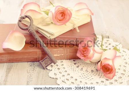 Fresh roses with old book and letters on color wooden table background. Vintage concept - stock photo
