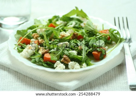 Fresh ruccola salad with baked pumpkin and goat cheese - stock photo