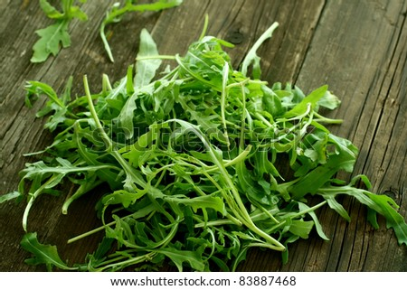 fresh rucola on old wooden boards - stock photo