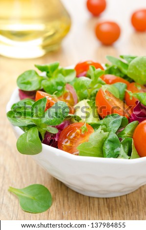 fresh salad and cherry tomatoes in a bowl, olive oil in the background, vertical