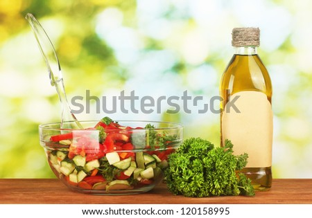 Fresh salad and oil on green background