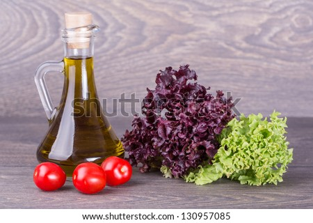 Fresh salad and oil on wooden background - stock photo