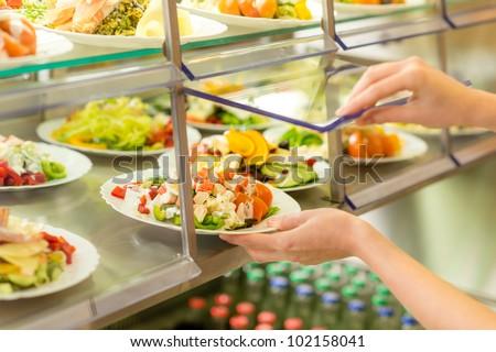 Fresh salad buffet self-service food display human hand take plate - stock photo