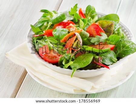 Fresh salad in a white bowl . - stock photo