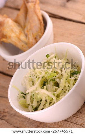 Fresh salad in a white bowl and chicken legs - stock photo