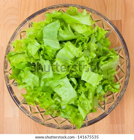 Fresh salad in glass plate on a wooden board