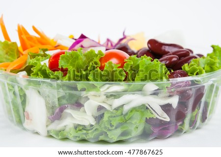 Fresh salad in plastic box packaging on white paper background.