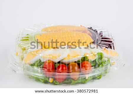 Fresh salad in plastic packaging on white paper background. - stock photo