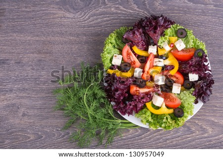 Fresh salad in white plate on wooden background - stock photo