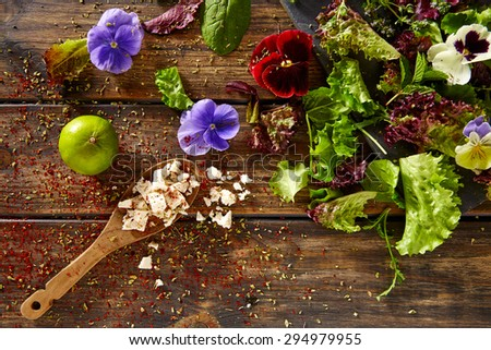 Fresh salad ingredients lettuce flowers spinach feta cheese on rustic wood - stock photo