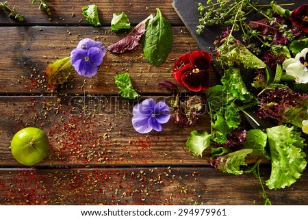 Fresh salad ingredients lettuce flowers spinach on rustic wood - stock photo