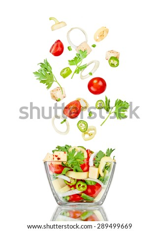 Fresh salad. Mixed falling vegetables in bowl on white backgroun