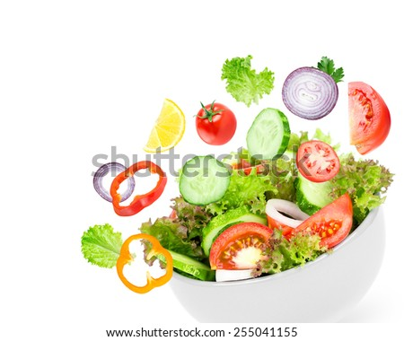Fresh salad. Mixed falling vegetables in bowl on white background - stock photo