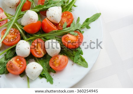 Fresh salad of arugula, cherry tomatoes and mozzarella on a white plate, top view