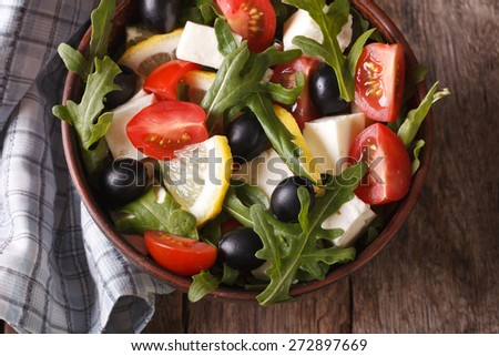 Fresh salad of arugula, feta, olives and tomatoes close-up, horizontal view from above