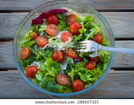 Fresh salad of cherry tomatoes and lettuce on a wooden background - stock photo