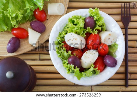 Fresh salad of heart of palm (palmito), cherry tomatoes and olives on white plate with black pepper and wooden fork on bamboo. Selective focus  - stock photo