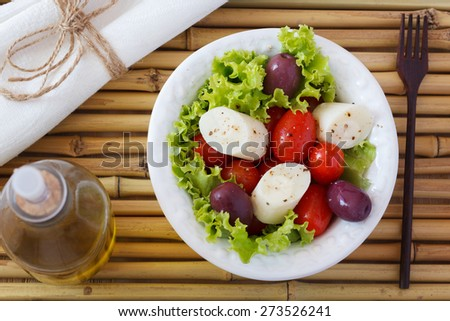 Fresh salad of heart of palm (palmito), cherry tomatoes, olives and black pepper on white plate with olive oil and wooden fork on bamboo. Selective focus  - stock photo
