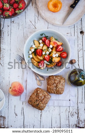 Fresh Salad of peach, strawberry, leaves of mint and goat cheese with whole burger bread served on rustic white surface from above. Rustic style  - stock photo