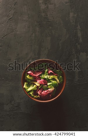 Fresh salad on a dark surface, top view. Helpful and simple food - stock photo