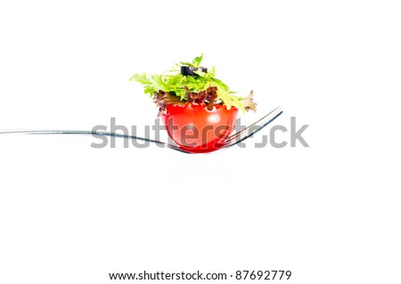 Fresh salad piled on half cherry  tomato on a fork - stock photo