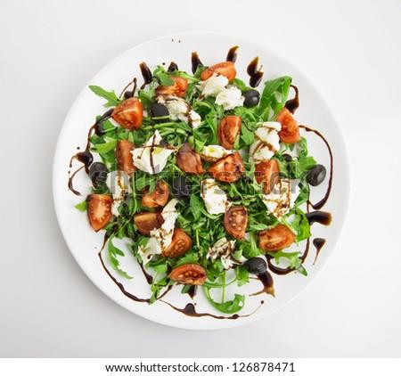 fresh salad, rucola, mozzarella, tomatos,olives, balsamic vinegar - stock photo