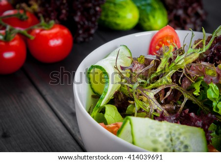 Fresh salad, vegetable organic healthy food on a wooden table with bunch of tomatoes and cucumbers - stock photo