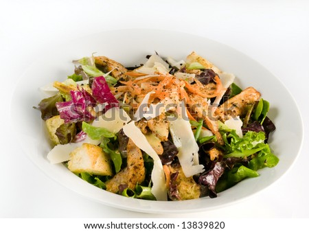 Fresh salad with assorted greens, fried pork, carrots, croutons, parmesan cheese, and honey mustard vinaigrette. - stock photo
