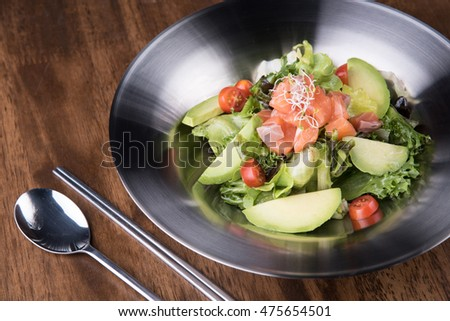 Fresh salad with avocado and salmon on wooden table