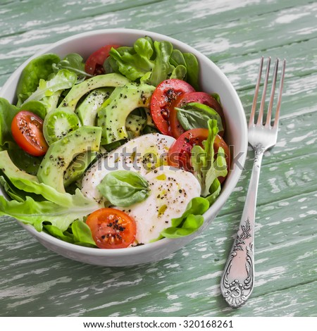 fresh salad with avocado, tomato and mozzarella, in a white bowl on bright wooden surface - stock photo