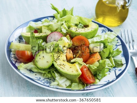 Fresh salad with avocado,tomatoes,lettuce,radish,carrot,onions and spices - stock photo
