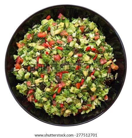 Fresh salad with broccoli, red pepper, avocado, dill, raisins, sunflower seeds in black plate. Isolated on white background - stock photo