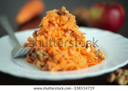 Fresh salad with carrot, apples and walnuts. Shallow depth of field. - stock photo