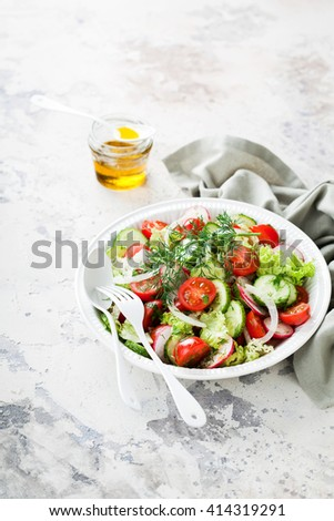 Fresh salad with cherry tomatoes, cucumbers, radishes, dill and olive oil, selective focus - stock photo