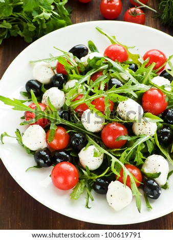 Fresh salad with cherry tomatoes, rucola, mozzarella and black olives. Shallow dof.