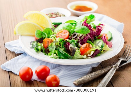 Fresh salad with cherry tomatoes, spinach, arugula, romaine and lettuce in a plate on rustic wooden background, selective focus - stock photo