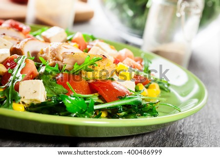 Fresh salad with chicken breast, arugula and tomato on a plate