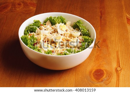 Fresh salad with chicken breast, cheese and eggs on wooden table - stock photo