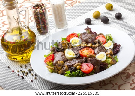 Fresh salad with chicken liver, mushrooms and vegetables. Delicious eating. - stock photo