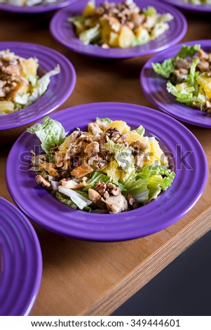 Fresh salad with chicken meat, oranges, walnuts, greens and herbs and olive oil on a bright colorful ceramic plates. Portion of salad on the background of cardboard with space for your text or menu - stock photo