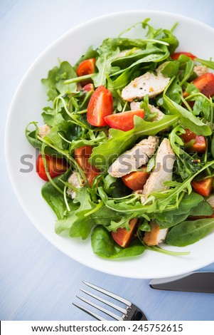 Fresh salad with chicken, tomato and greens (spinach, arugula) on blue wooden background top view. Healthy food. - stock photo