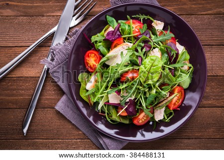 Fresh salad with chicken, tomatoes and mixed greens (arugula, mesclun, mache) on wooden background top view. Healthy food. - stock photo