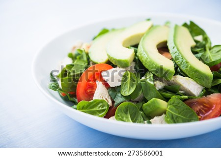 Fresh salad with chicken, tomatoes, spinach and avocado on blue wooden background close up. Healthy food. - stock photo