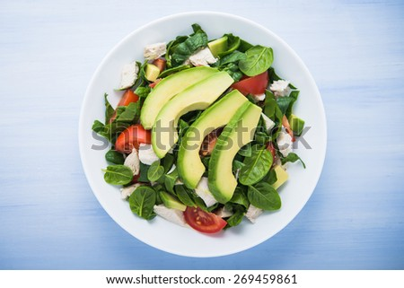 Fresh salad with chicken, tomatoes, spinach and avocado on blue wooden background top view. Healthy food. - stock photo