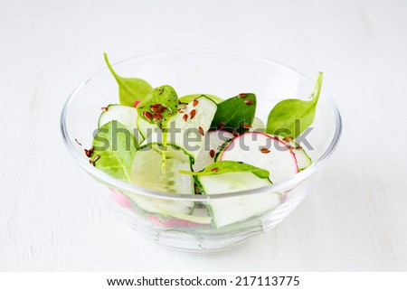 Fresh salad with cucumbers, radishes and basil, food close up