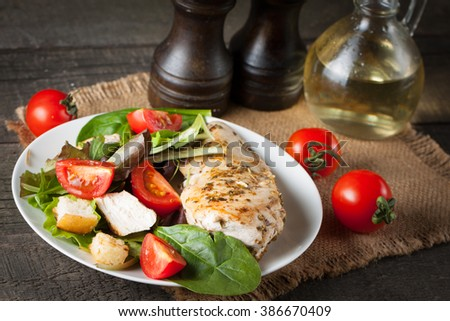 Fresh salad with delicious chicken breast, ruccola, spinach, cabbage, arugula and tomato on wooden background. Oil, salt and pepper. - stock photo