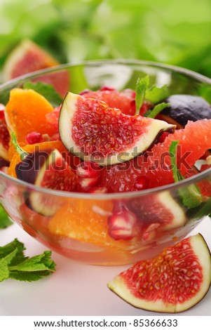 Fresh salad with figs, grapefruit, tangerine and pomegranate with dressing of honey and juice - stock photo