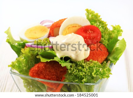 Fresh salad with fried breaded cheese and sliced boiled egg - stock photo