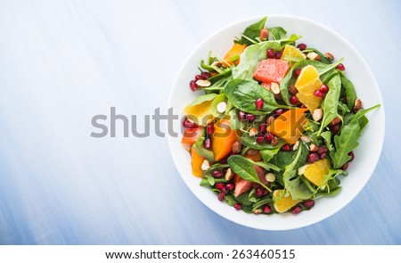 Fresh salad with fruits and greens on blue wooden background top view. Healthy food. Space for text. - stock photo