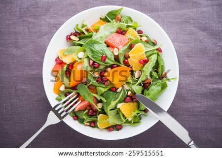 Fresh salad with fruits and greens on dark canvas background top view. Healthy food. - stock photo